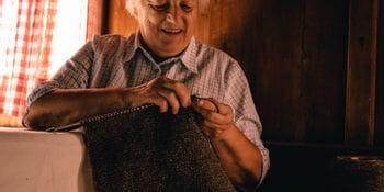 Eine ältere Dame beim Stricken mit Wolle