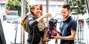 Dame gibt alte Skiausrüstung bei Bründl Sports zurück