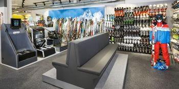 große Sitzbank im Vordergrund, Skischuhe und Ski im Hintergrund <br/>