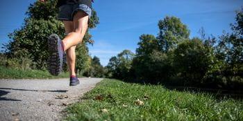 a person runs along a path in the summer