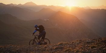 a mountain-biker rides through the mountains while the sun sets