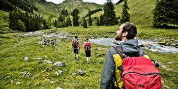 junge Leute durchqueren ein grünes Flusstal in den Bergen