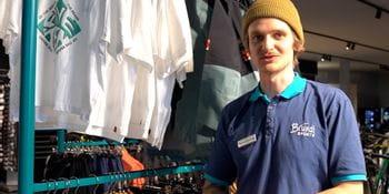 Bruendl Sports Mitarbeiter steht vor einer Wand und stellt Produkte von Adidas Five Ten vor.