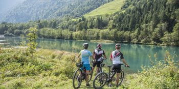 three cyclists are standing at the shore of a lake
