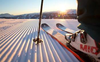 ein Skifahrer fährt auf einer frisch präparierten Piste