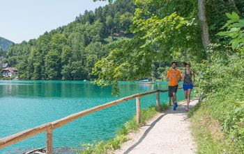 "two people are running at the lake ""Wolfangsee"""