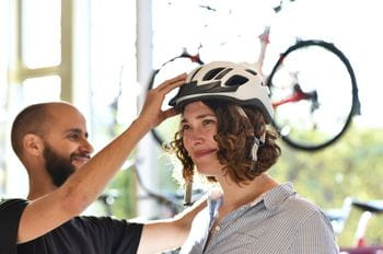 a woman is fitting on a bycicle helmet