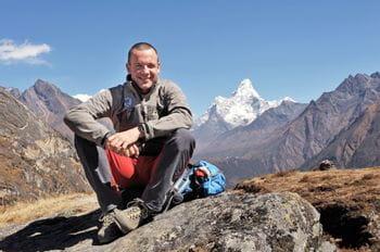 Markus Amon sitzt gemütlich am Berg, hinter ihm ein wunderschönes Berg Panorama.