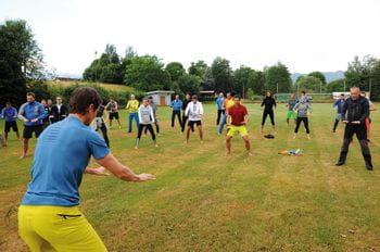 mehrere Personen machen gymnastische Übungen auf Rasen