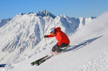 ein Skifahrer fährt rasant einen Hang hinab