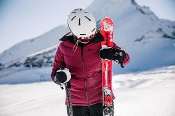 Eine Skifahrerin steht im Schnee, in der einen Hand ihre Ski, in der anderen Hand ihre Skistöcke