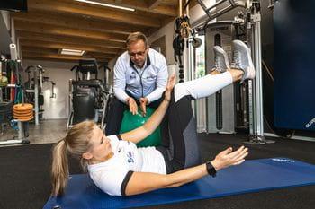 Eine junge Dame bei einer Bauchmuskel Übung unterstützt von Gernot Schweizer