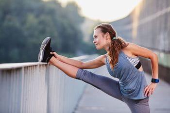 eine Läuferin dehnt sich auf einem Geländer