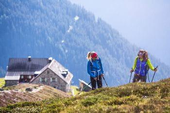 zwei Frauen erfreuen sich des Wanderns, im Hintergrund eine Alpenhütte