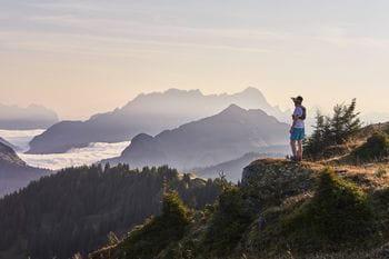 ein Trailläufer blickt in die Ferne und genießt den Ausblick auf die Alpen