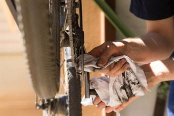 a bycicle chain is cleaned with a towel