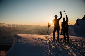 Two ski moutaineers on the summit during sundown in the National Park Hohe Tauern