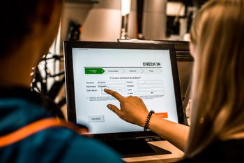 A couple is typing in their names at the check-in station