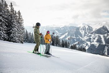 two skiers are talking to each other on a ski slope, a snowy landscape in the background
