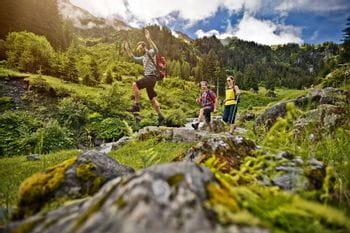 drei junge Leute wandern vergnügt durch ein dicht bewaldetes Gebiet in den Alpen