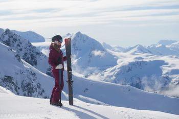 Eine Dame mit einem Paar Rossignol Soul 7 Ski in der Hand genießt das Bergpanorama