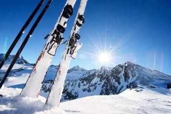 Skier in der Piste steckend, im Hintergrund Berge und die Sonne