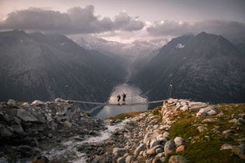 two hikers on a suspension bridge in the mountains