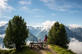 two bikers are making a break while on a mountain tour