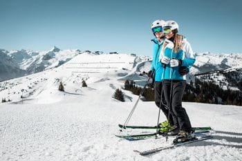 zwei Skifahrer stehen vor einer Abfahrt