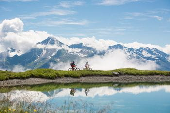 two biker are riding alongside a mountain lake, wherein the mountains are mirrored.