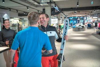 Ein Paar bekommt von einem Bründl Sports Verleihmitarbeiter die Verleihski überreicht