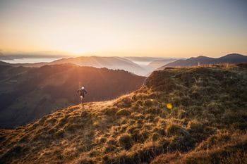 ein Trailläufer befindet sich entlang eines Feldweges auf einem Berghang, im Hintergrund der Sonnenuntergang