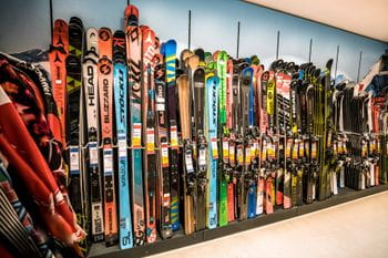 A lot of skis lined up on a wall