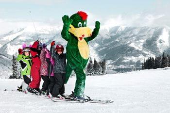 das Bild zeigt einer Kindergruppe beim Skifahren lernen