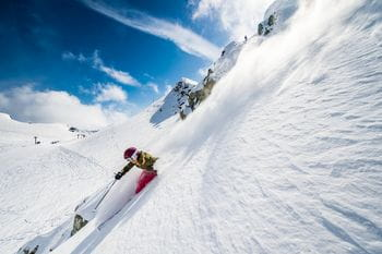 A woman is skiing through powder next to the slopes