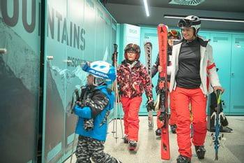 Eine Familie geht nach einem Skitag ins Bründl Sports Skidepot und lagert dort ihre Ski und Skischuhe ein
