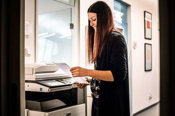 ein Lehrlung druckt ein Blatt Papier im Büro aus