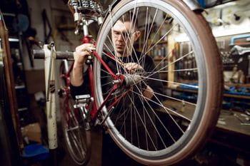 ein Rad ist in einer Werkstatt aufgehängt, während ein Mechaniker daran arbeitet
