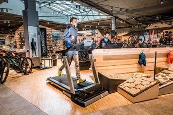 Ein Läufer läuft auf einem Laufband im Shop, im Hintergrund analysiert der Mitarbeiter den Laufstil am Computer