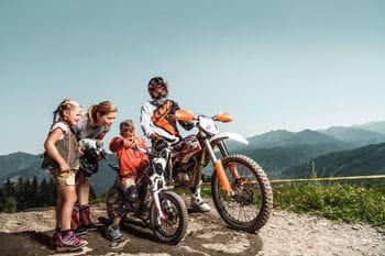 ein Motocrossfahrer und zwei Kinder