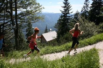 two women are running on a path in the woods