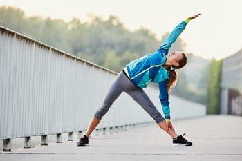 eine Läuferin dehnt sich im Stehen auf Asphalt