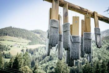 Ortovox Wollhandschuhe auf einem Holzgestellt aufgehängt