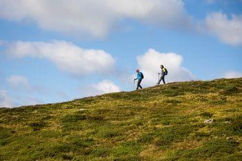 zwei Wanderer vor einem blauen, wolkenversetzten Himmel