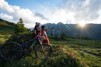 two bikers are looking at mountain landscape
