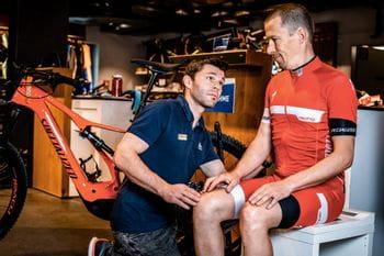 Ein Radfahrer sitzt auf dem Gerät zur Sitzknochenvermessung und wird vom Verkäufer in die richtige Position gebracht
