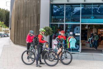 Eine Gruppe von Radfahrern versammelt sich vor dem Shop