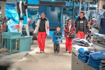 A family dressed in ski clothes enters a sports shop