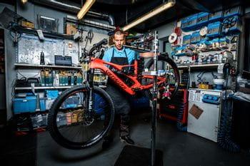 Ein Mitarbeiter mit einem Fahrrad in der Werkstatt