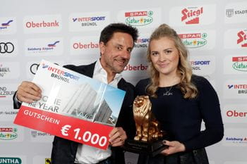 Christoph Bründl and Valentina Höll showing a huge shopping voucher of Bründl Sports and the famous Leonidas lion